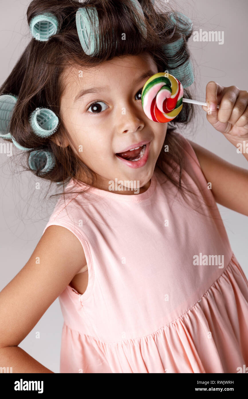 bd36cf4a8 Funny little child girl in pink dress and hair curlers holding lollipop on  gray background.