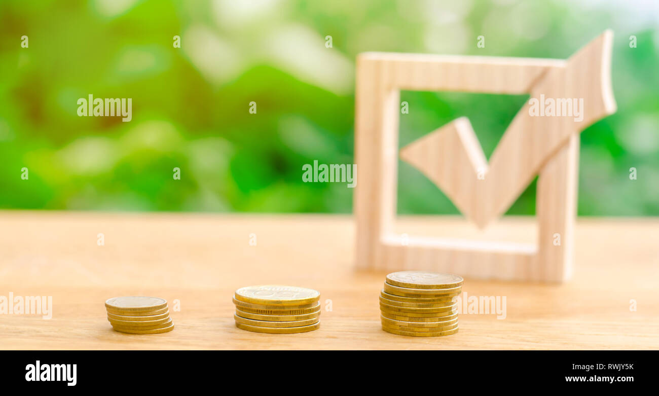 Wooden check mark and stacks of coins. Lobbying the adoption of regulations and laws. Illegal money laundering and control of financial flows. Interes - Stock Image