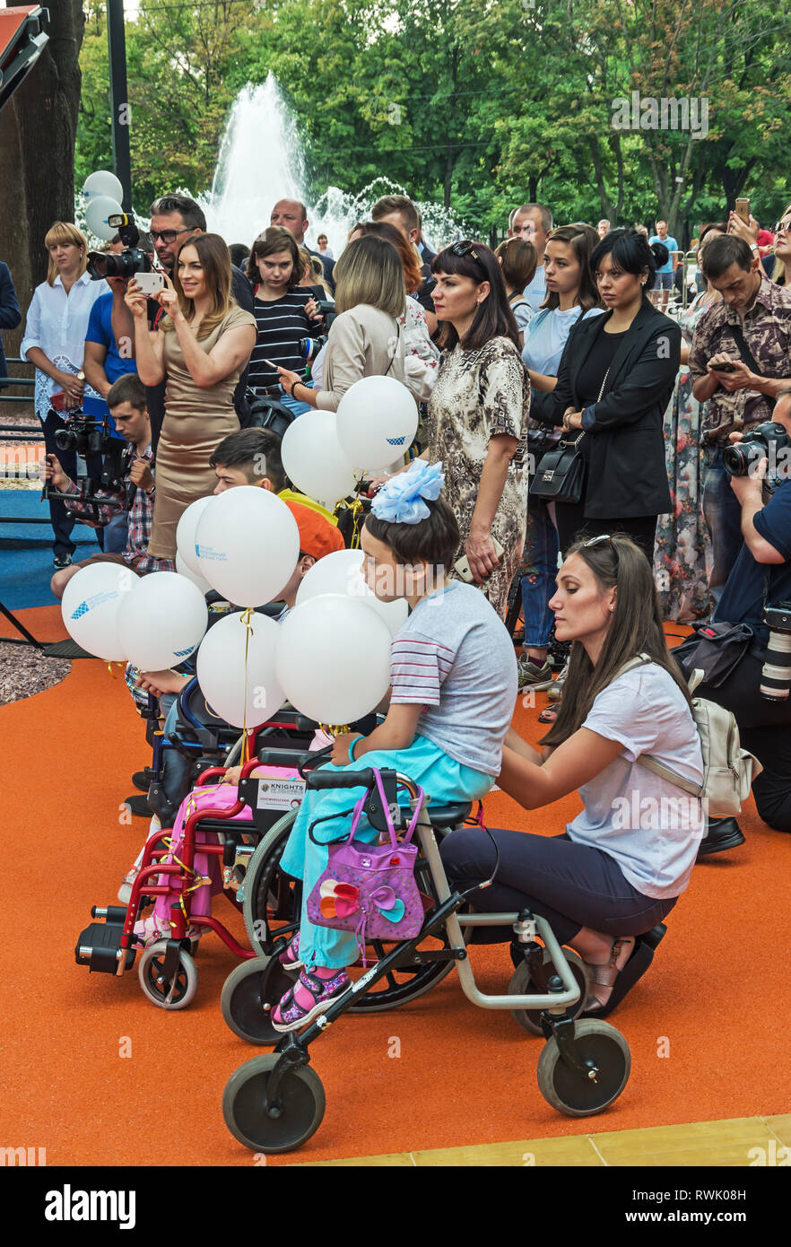 Dnipro, Ukraine - June 27, 2018: Cute kids in wheelchairs at inclusive park for children with special needs - Stock Image
