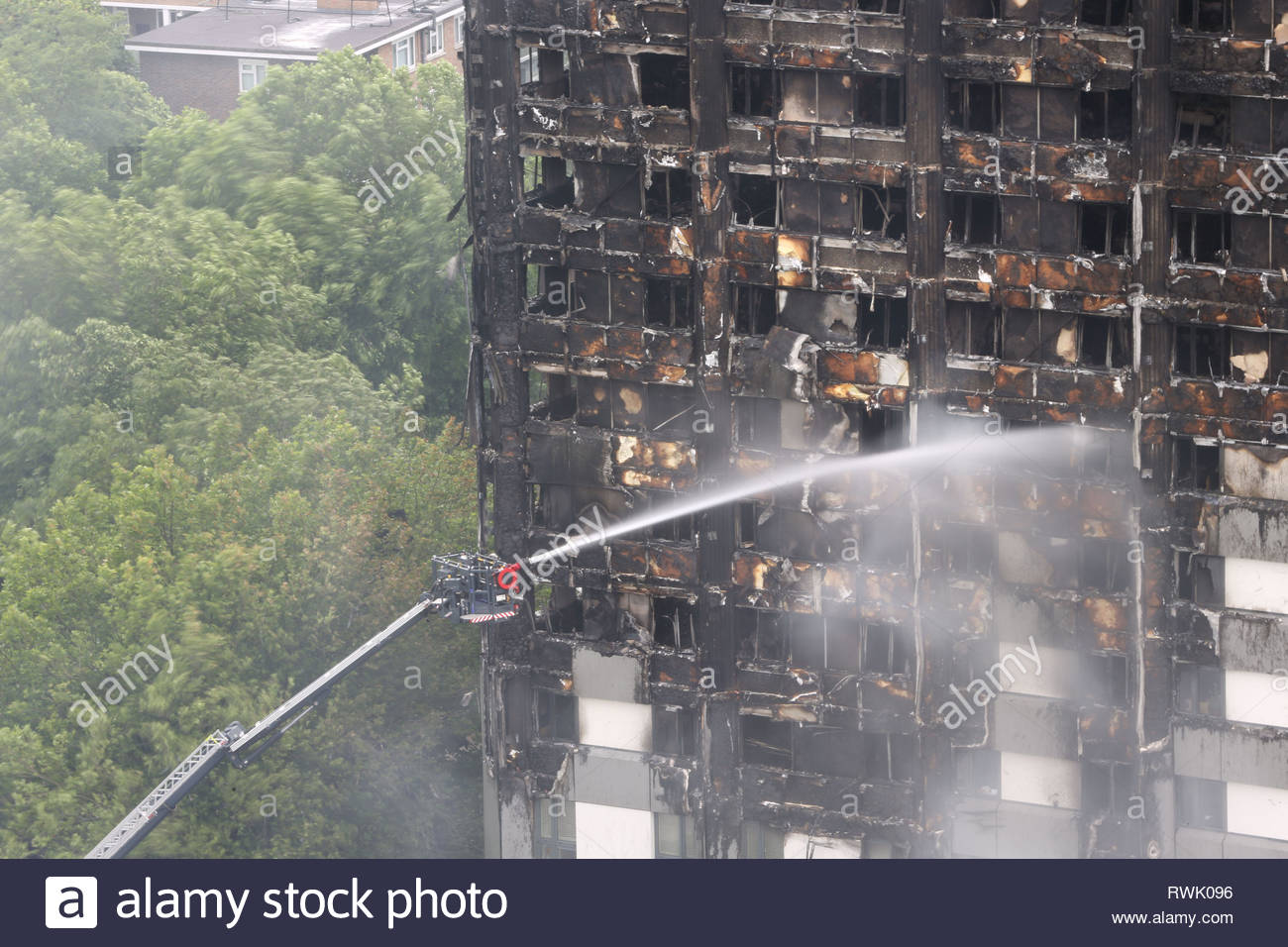 File photo dated 15/06/17 of water being sprayed on Grenfell Tower after the fire at the tower block. The Metropolitan Police said the criminal investigation into the fire is 'unlikely' to submit a file to the Crown Prosecution Service 'sooner than the latter part of 2021' after the conclusion of the second phase of the independent inquiry. - Stock Image