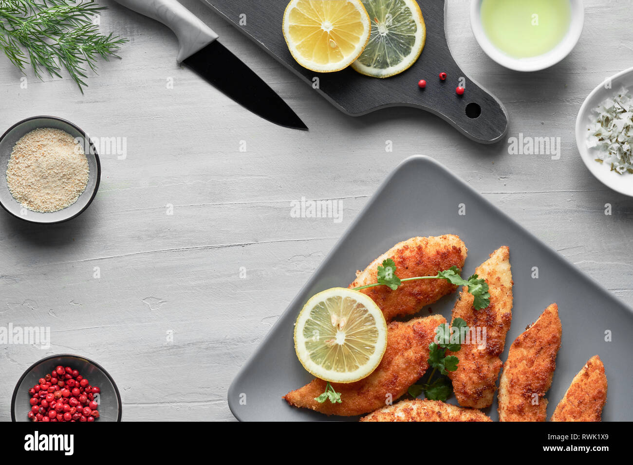 Breaded chicken stripes with breading, cooking oil, salt, pink pepper, dill and lemon, flat lay on light background - Stock Image