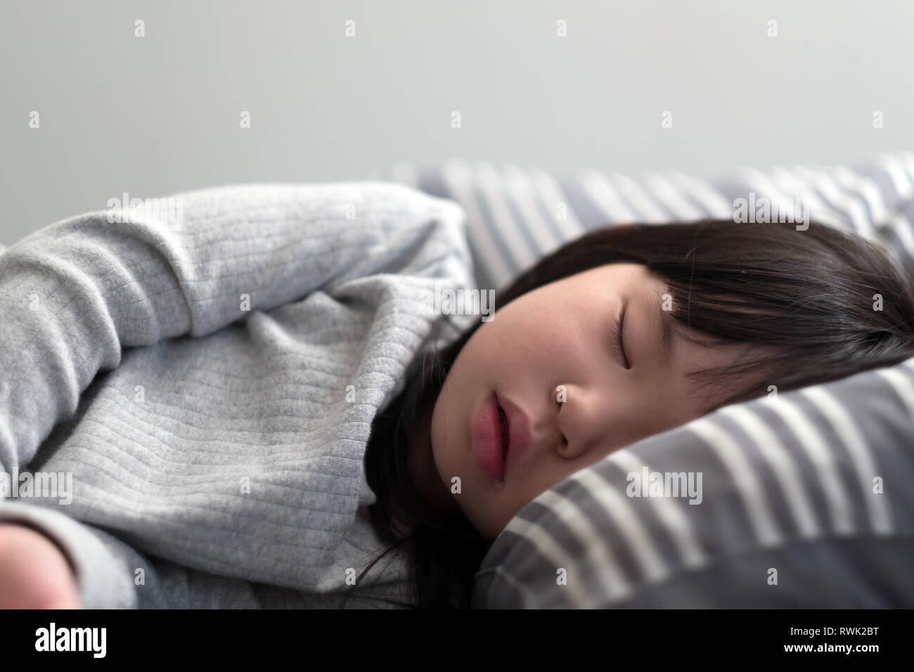 Child girl sleeping on bed - Stock Image