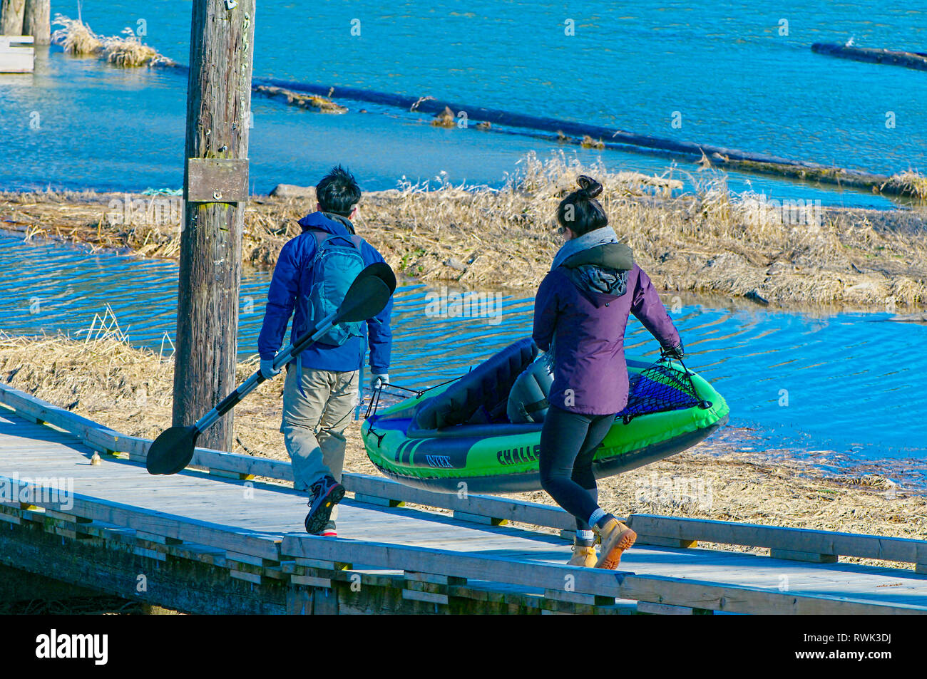 Young Asian couple carrying an inflatable kayak along a wooden ramp. Grant Narrows Regional Park, Pitt Meadows, British Columbia, Canada Stock Photo