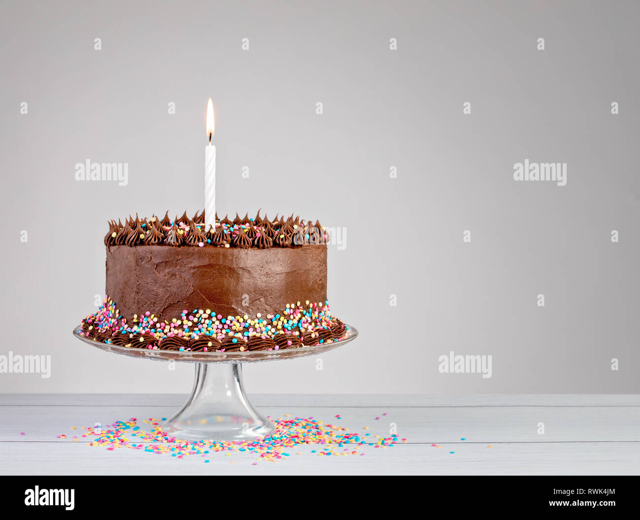 Chocolate Birthday Cake With Colorful Sprinkles And Candle Over White Background