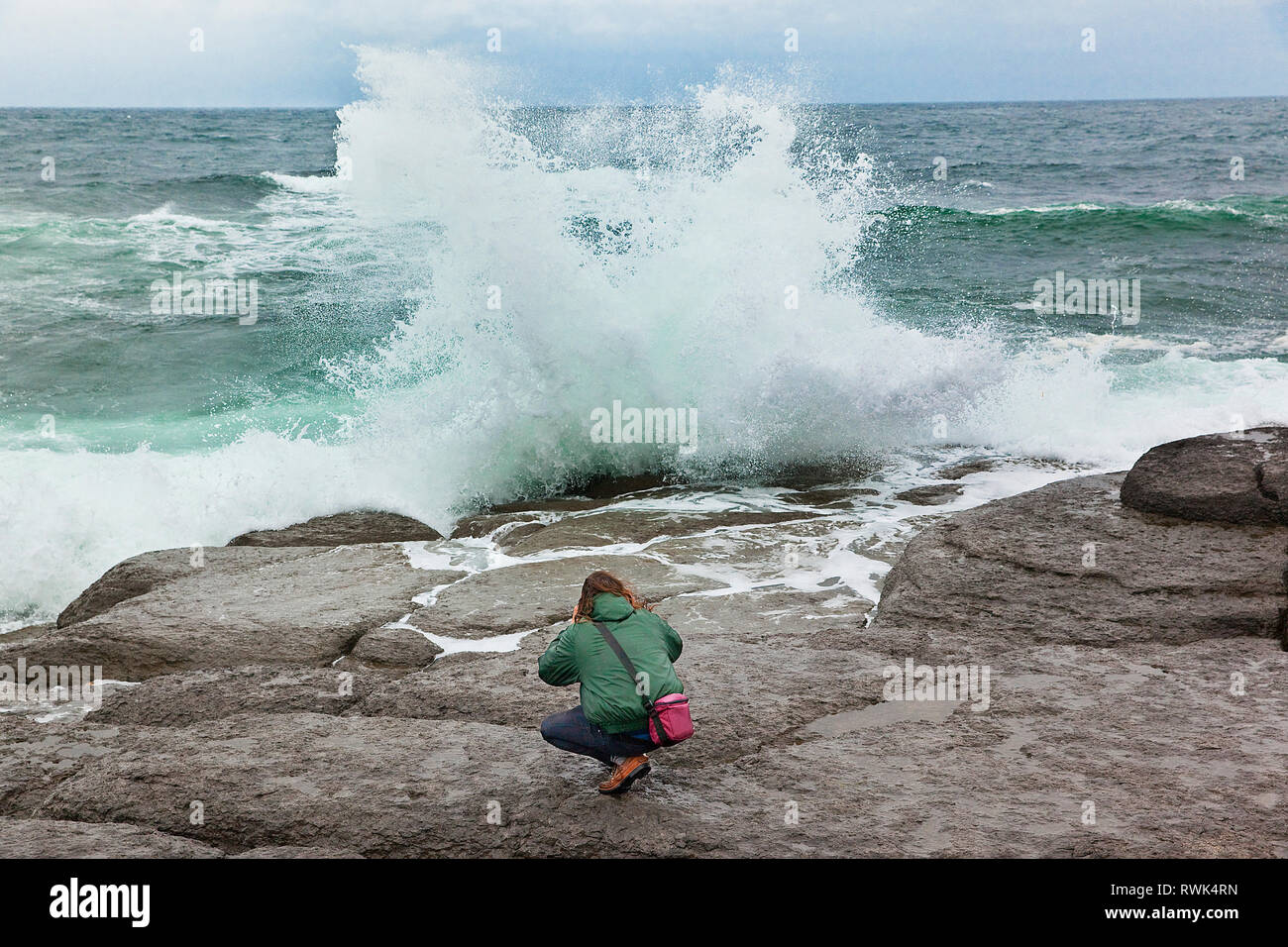 Young man crouched on a rock ledge in an attempt to photograph crashing waves up close. Port au Choix National Historic Site, Port au Choix, Newfoundland, Canada - Stock Image