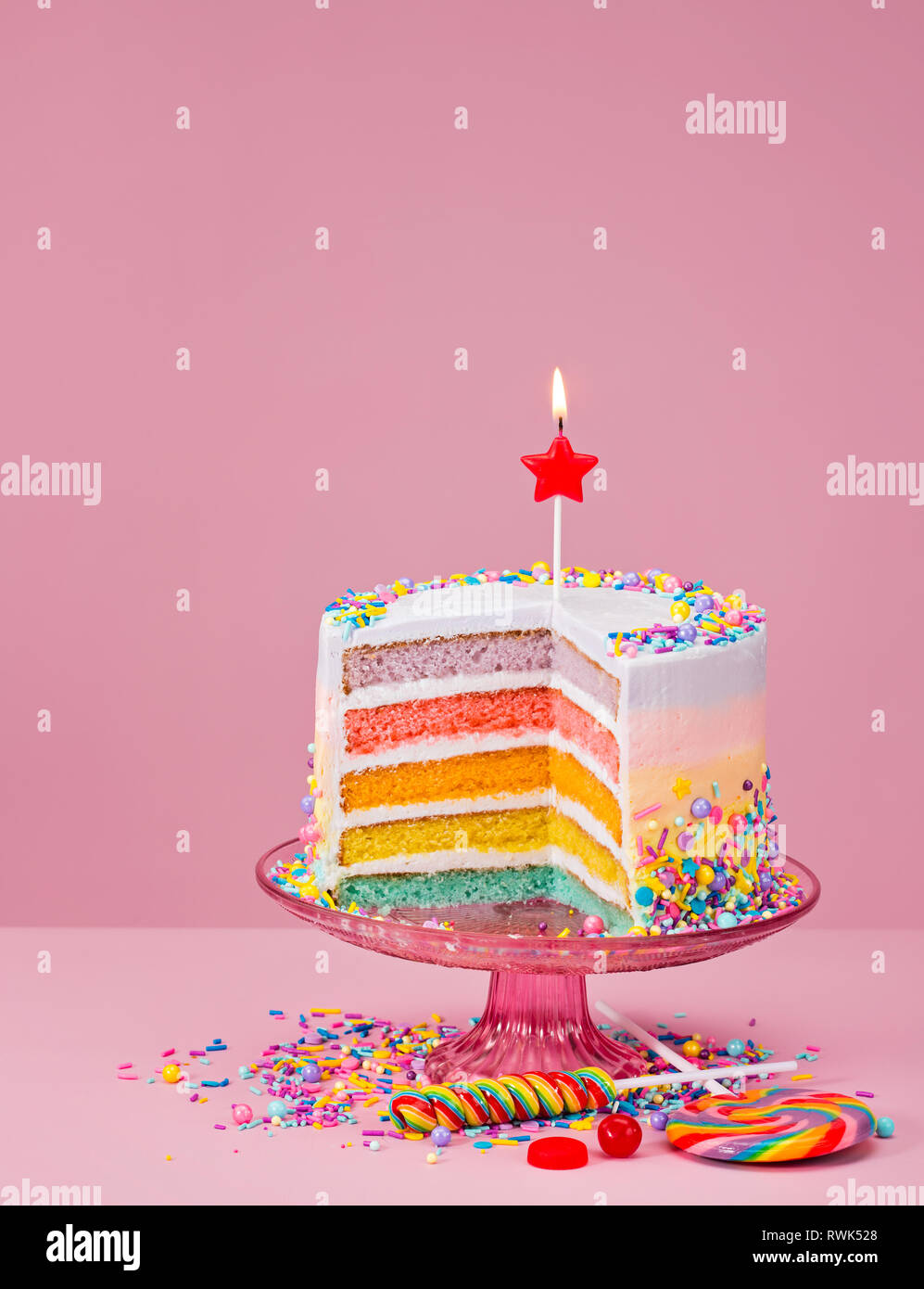 Colorful Layered Birthday Cake With Sprinkles And Candy Over A Pink Background