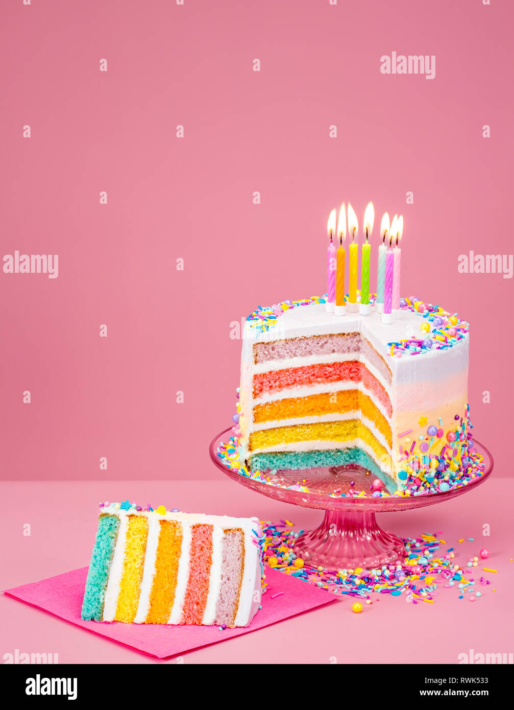 Colorful Rainbow Birthday Cake With Candles Over A Pink Background