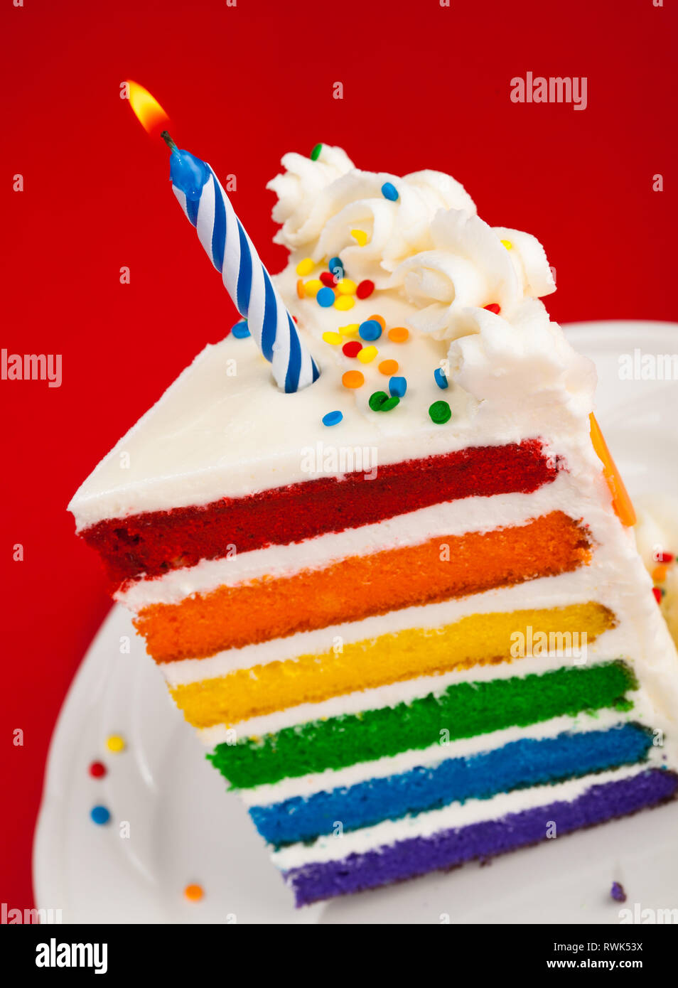 Rainbow Layer Birthday Cake Slice With Candle On A Red Background