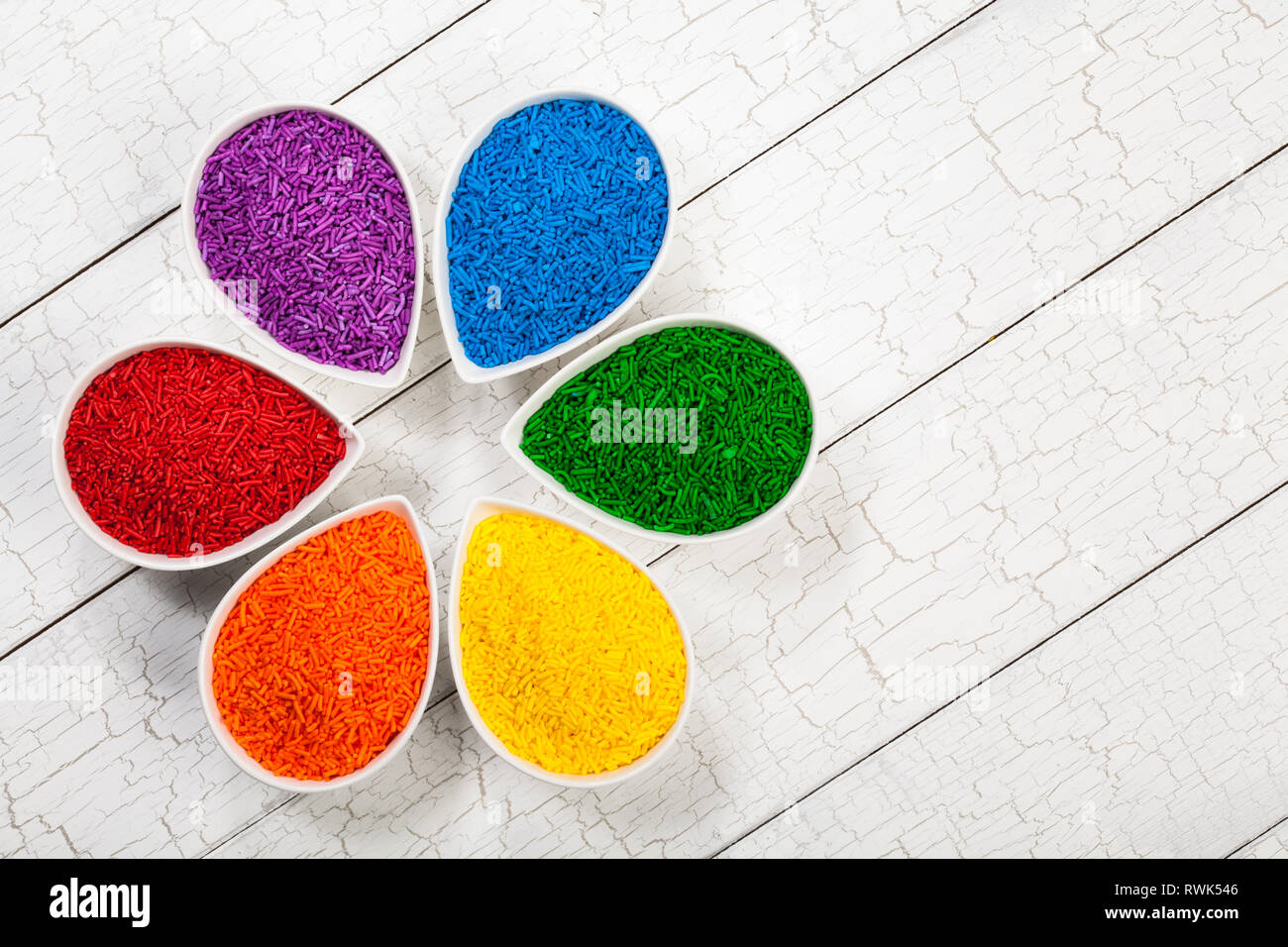 A rainbow assortment of colourful baking sprinkles used for decorating cookies and cakes in petal shaped bowls - Stock Image
