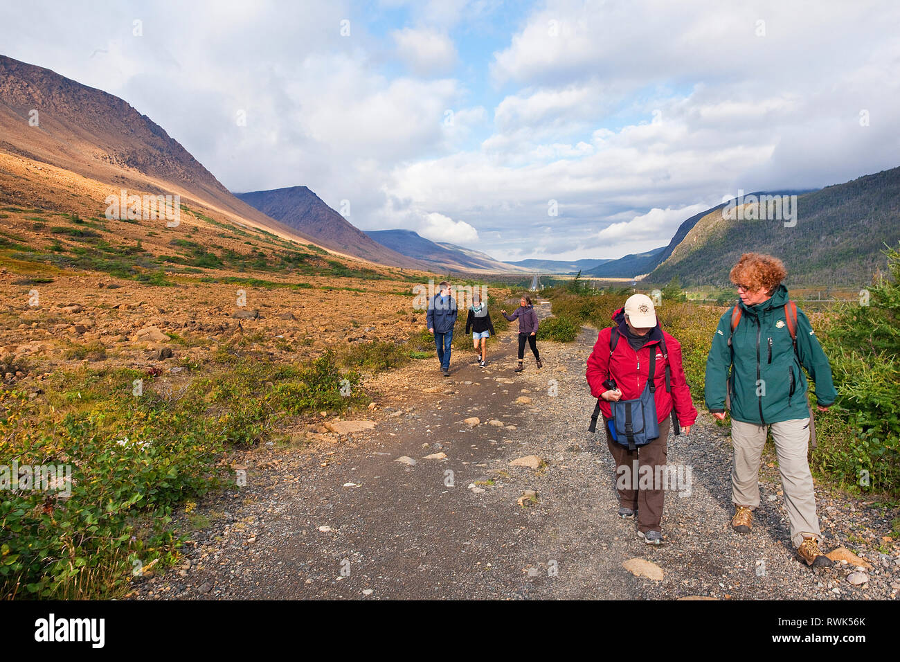 Parks Canada interpreter Kristen Oravec leading a small group of visitors along the Tablelands Trail in Gros Morne National Park, Newfoundland, Canada - Stock Image