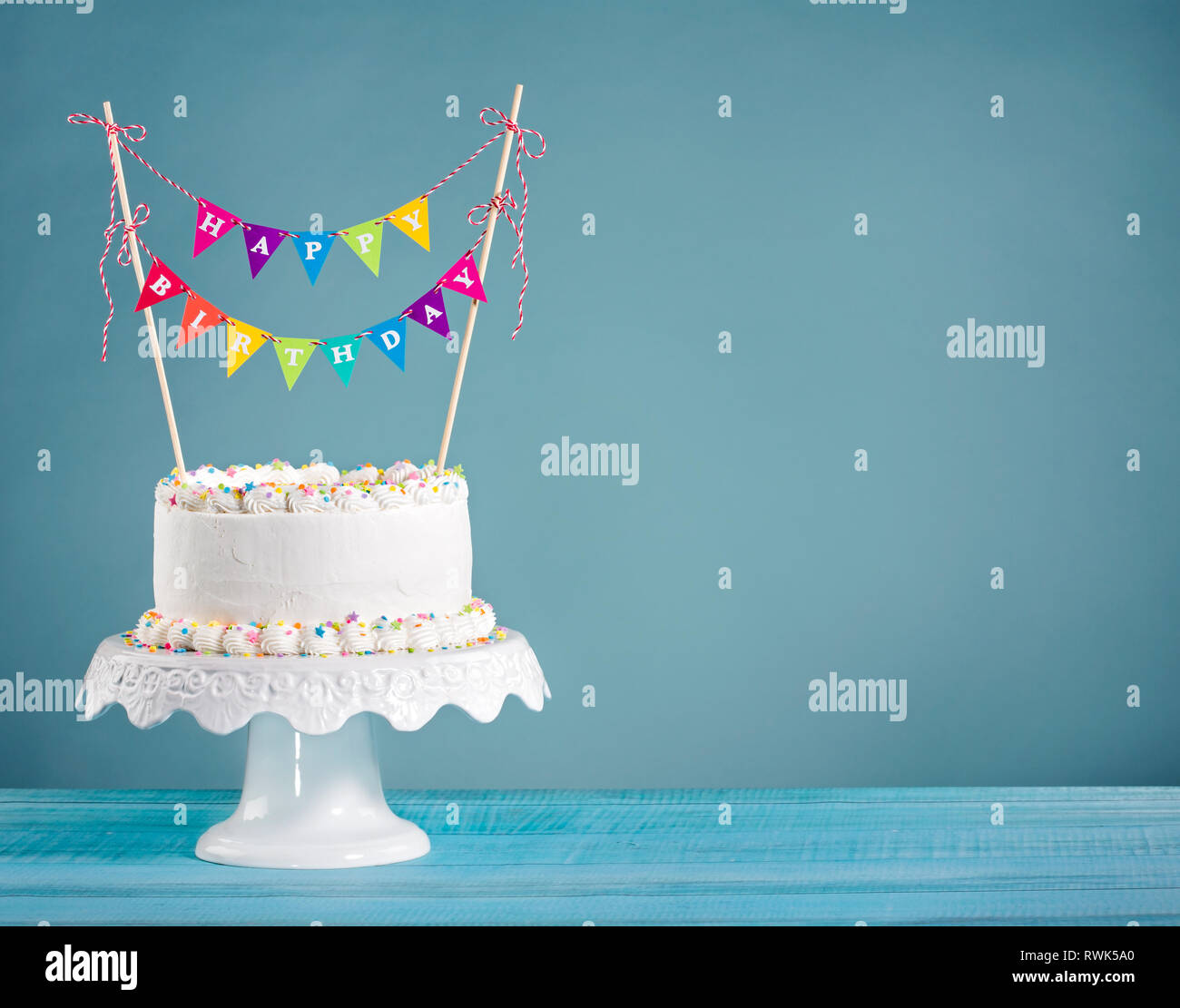 White Buttercream birthday cake with colorful bunting and