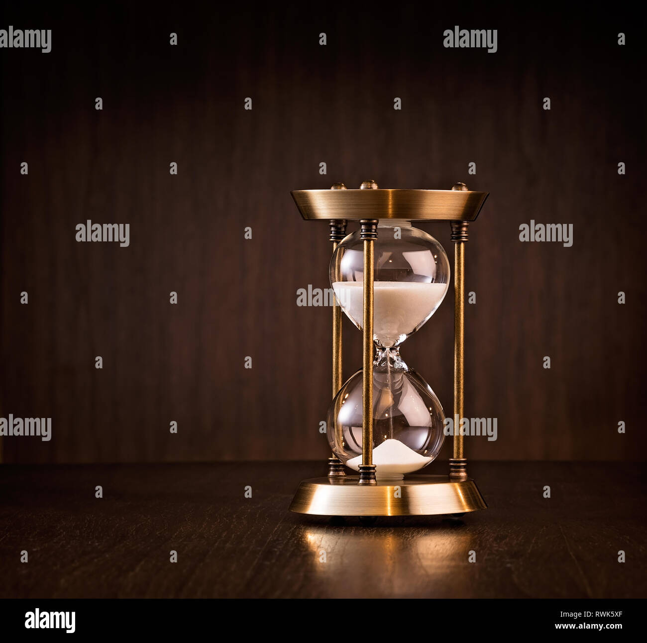 Hourglass measuring time passing.  Business deadline or running out of time concept. - Stock Image