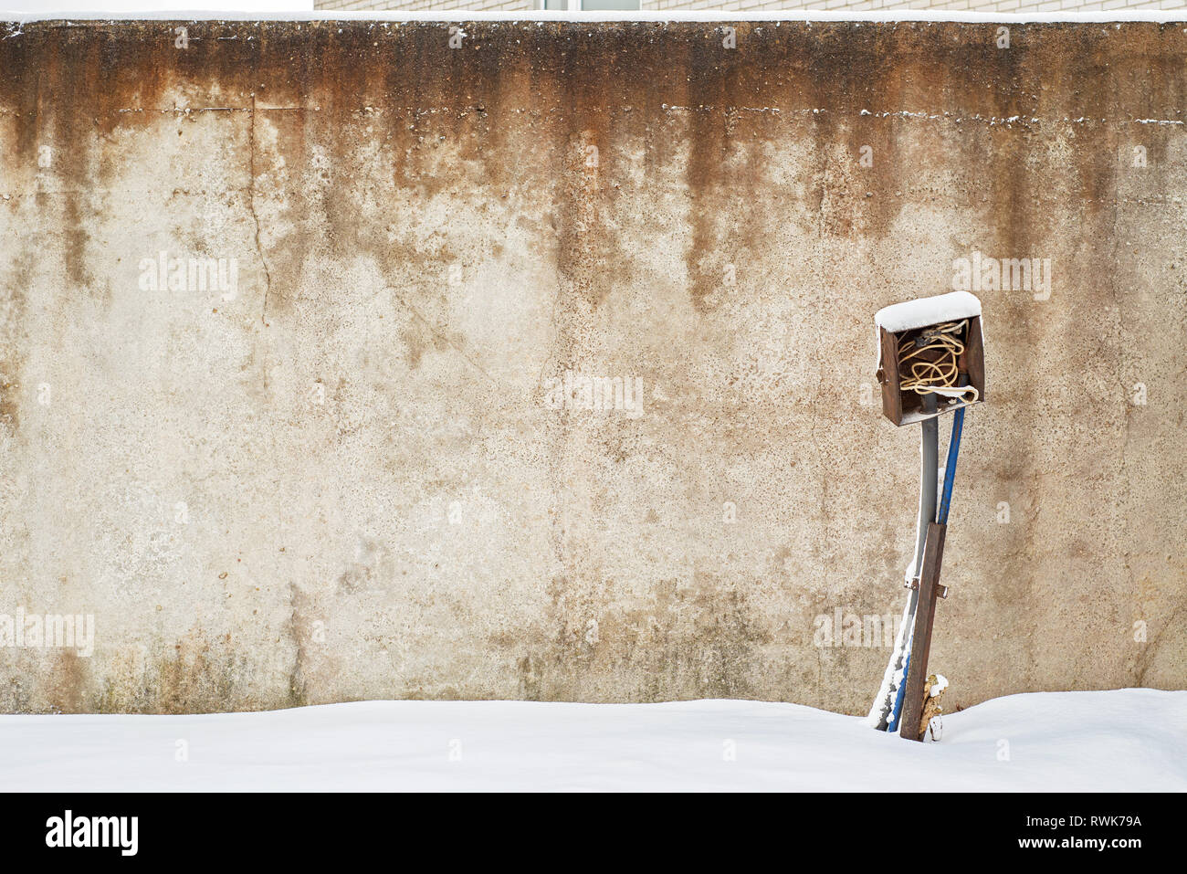 abandoned grunge house with electrical equipment near the wall in winter Stock Photo