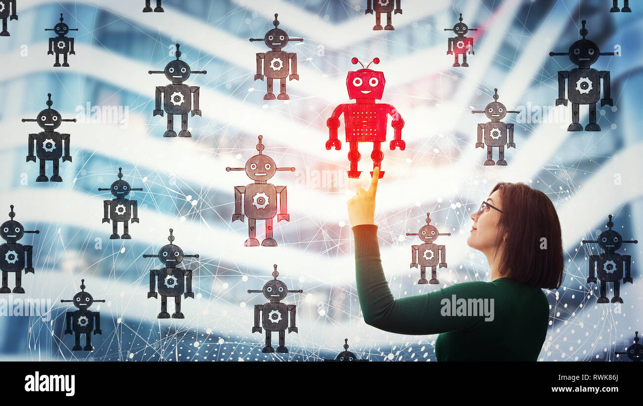 Smiling businesswoman pointing finger up, choosing a different robot. Employee choice, group of artificial intellect replace human, leadership concept - Stock Image