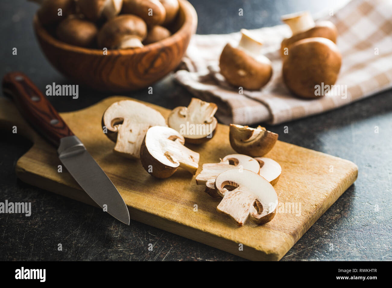 Fresh sliced champignon mushrooms on cutting board. Stock Photo