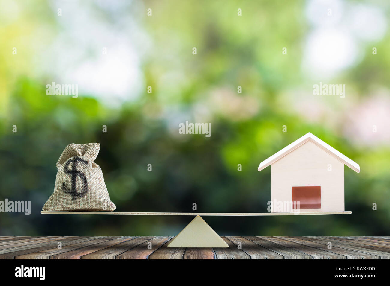 Home loan, home to money, Change real estate into cash concept. US Dollar in sack bag, Wooden house model on balance scales on wood table. Balance hom - Stock Image