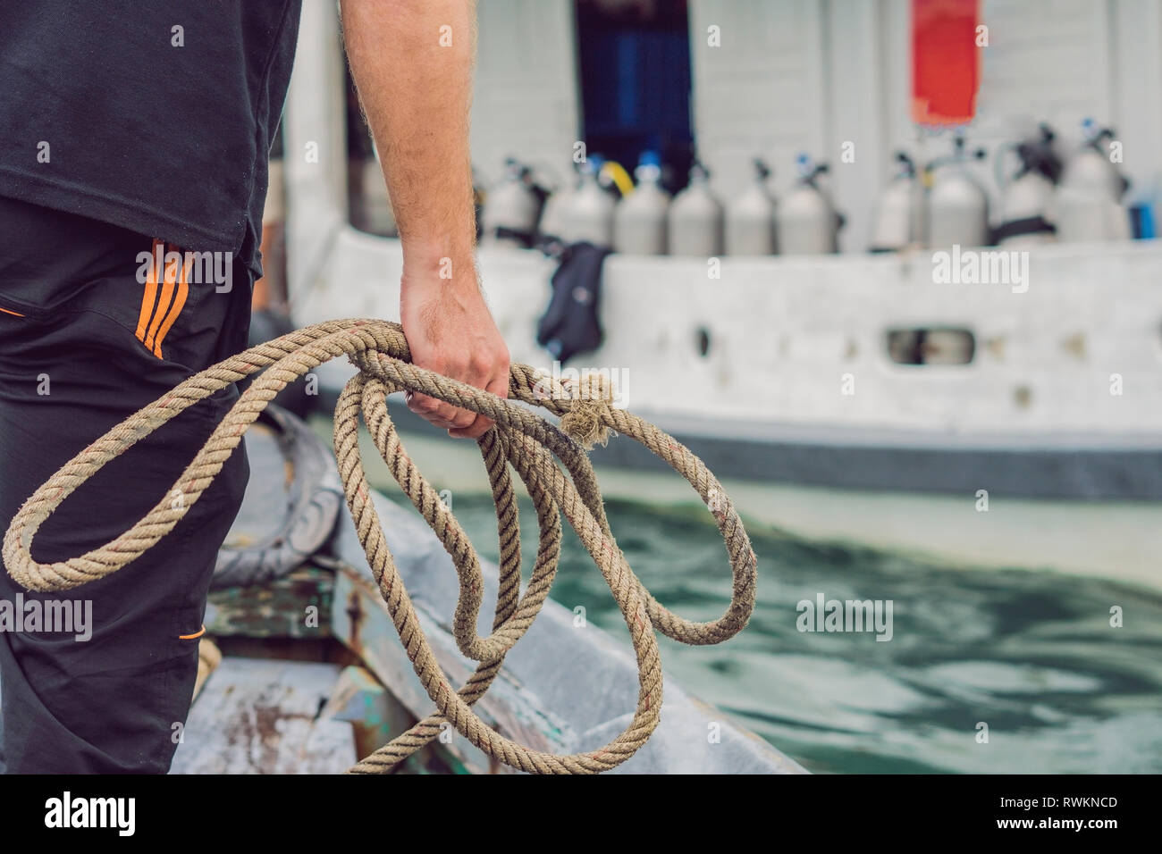 A man throws a rope to moor on a diver ship - Stock Image