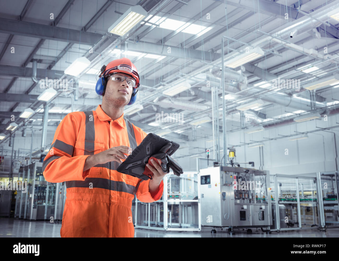 Composite image of engineer in manufacturing plant with digital tablet - Stock Image