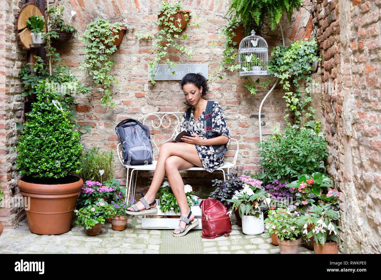 Woman enjoying peaceful corner with plants, Città della Pieve, Umbria, Italy - Stock Image