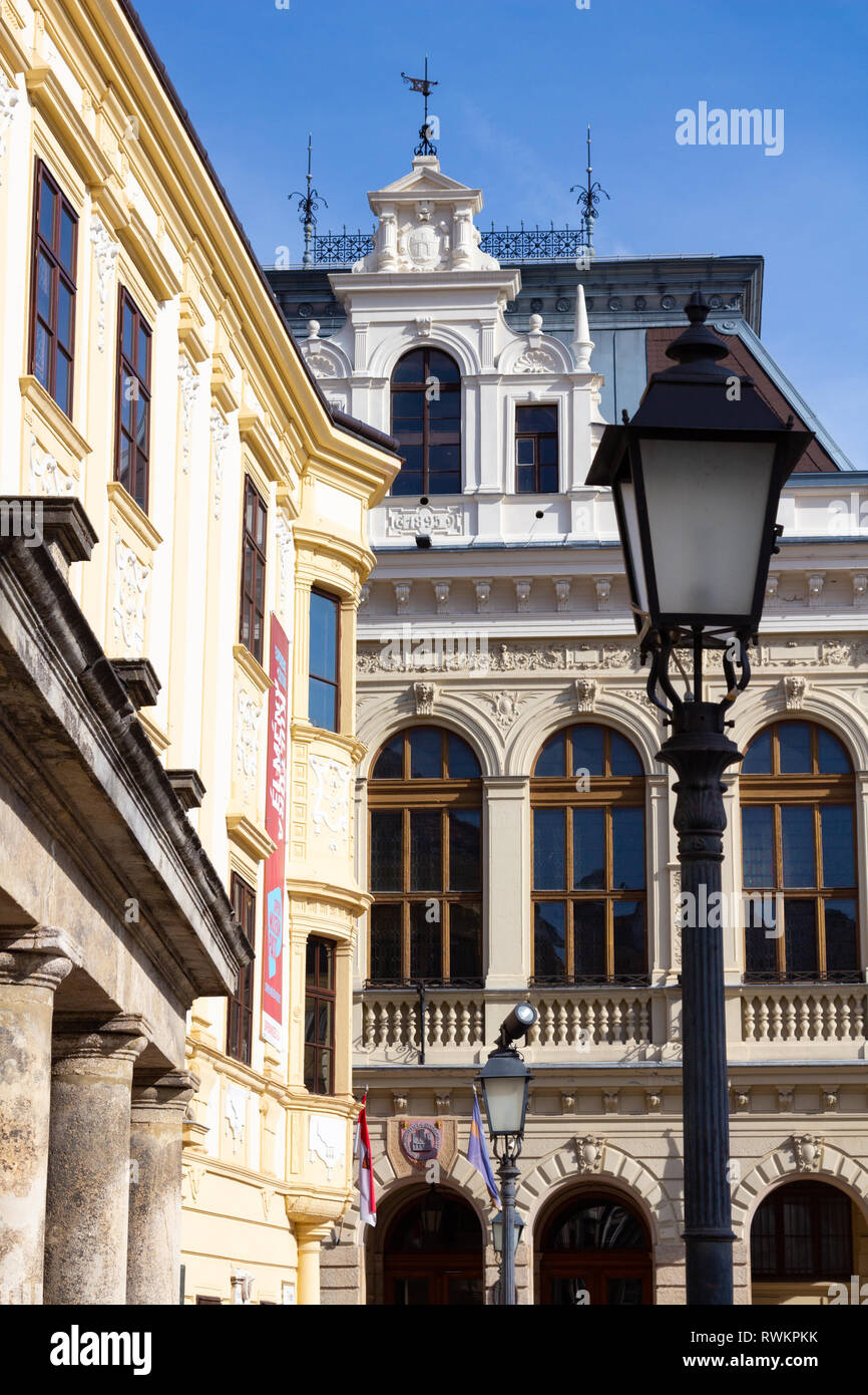 Detail of the Neo-Renaissance town hall in Sopron, Hungary, with the Baroque Storno House and lamp-standards - Stock Image