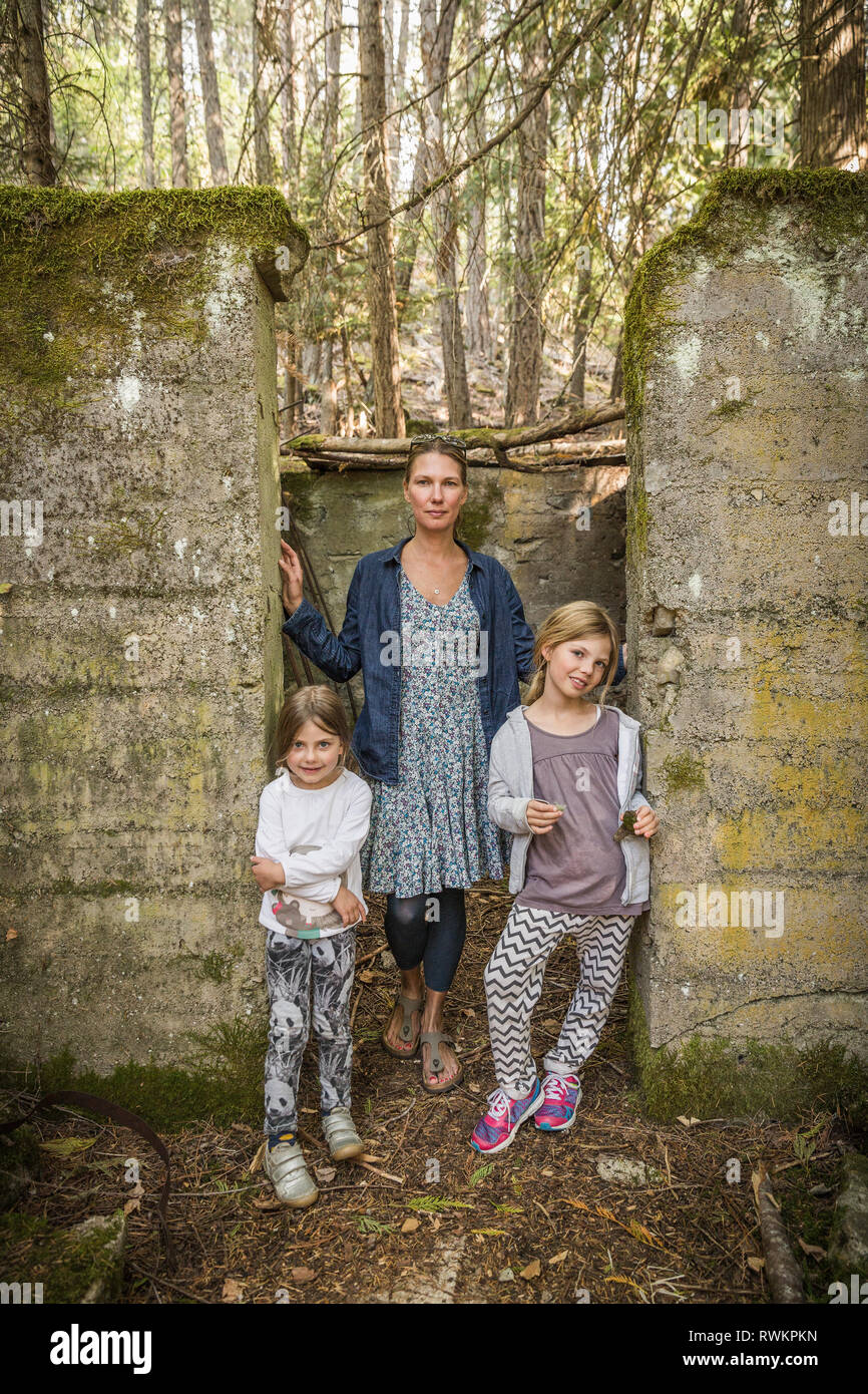 Woman and two daughters standing in derelict doorway in forest, Sandpoint, Idaho, USA - Stock Image