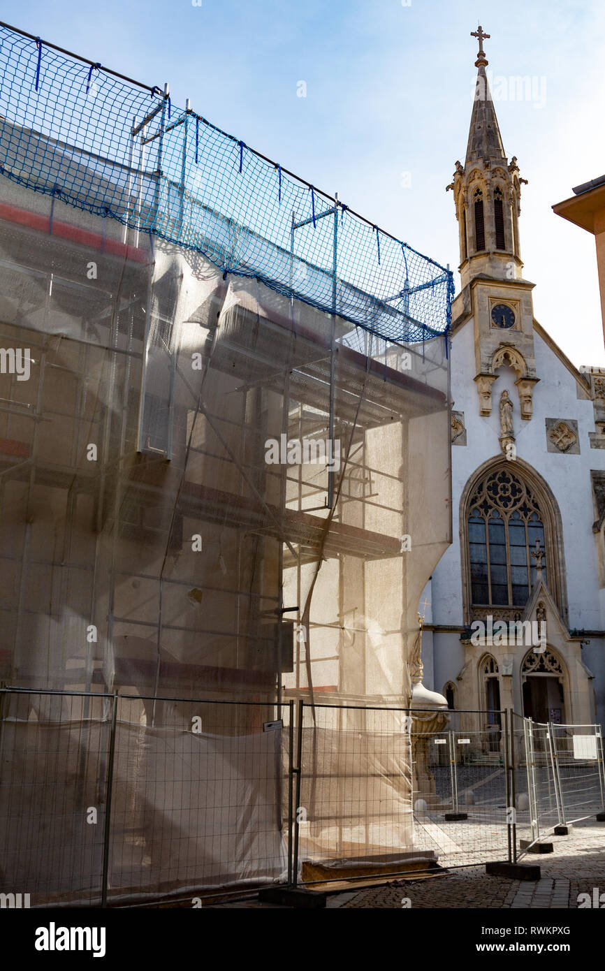 The so called Arcaded House during renovation, scaffolding. Orsolya tér, Sopron, Hungary. The Ursuline Church in the background. - Stock Image