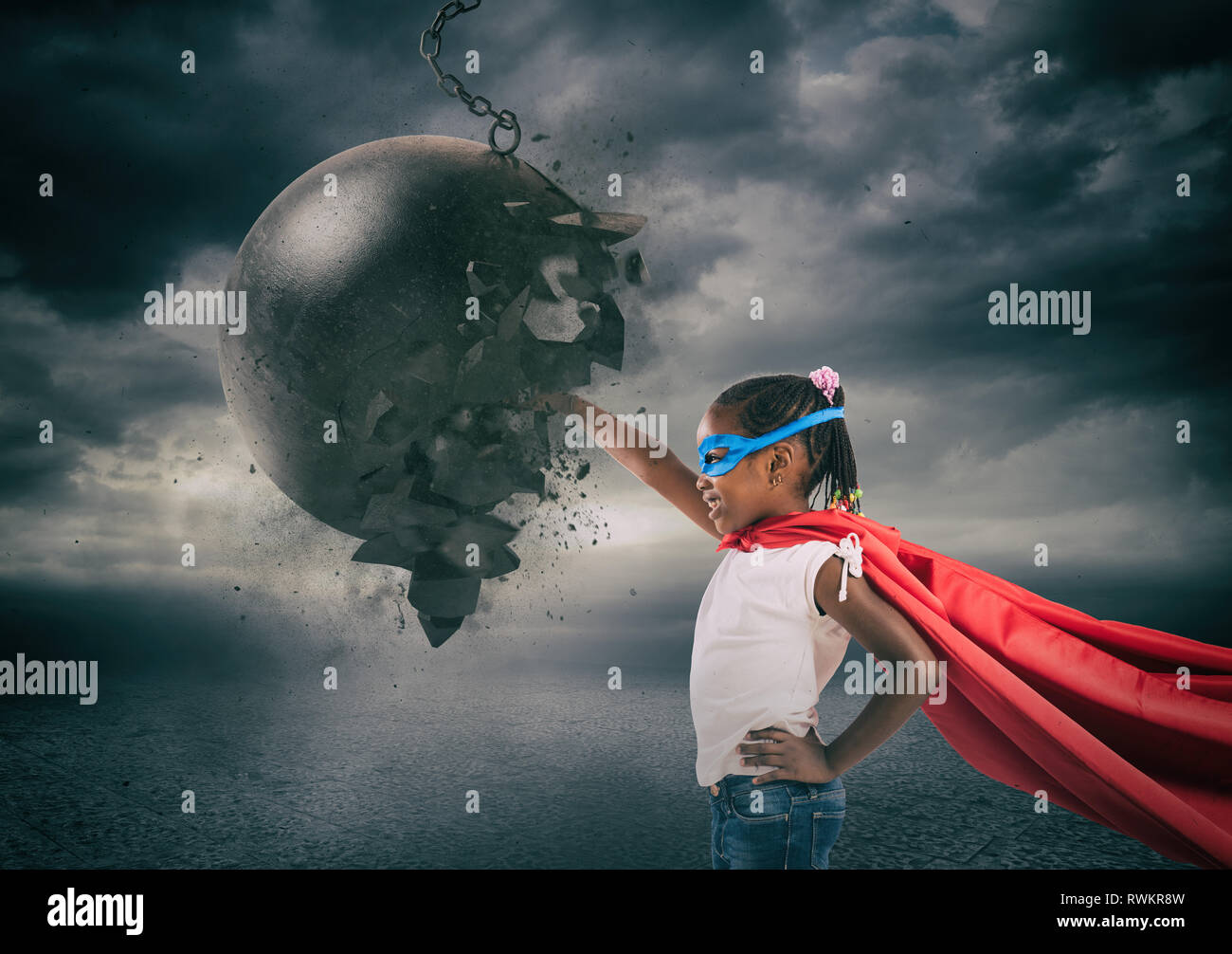 Power and determination of a super hero child against a wrecking ball - Stock Image