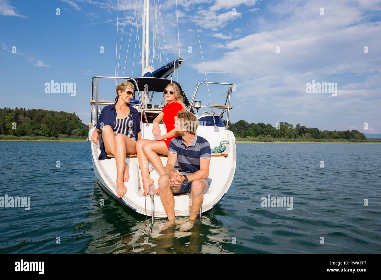 Young man and adult women sitting chatting on sailboat on Chiemsee lake, Bavaria, Germany - Stock Image