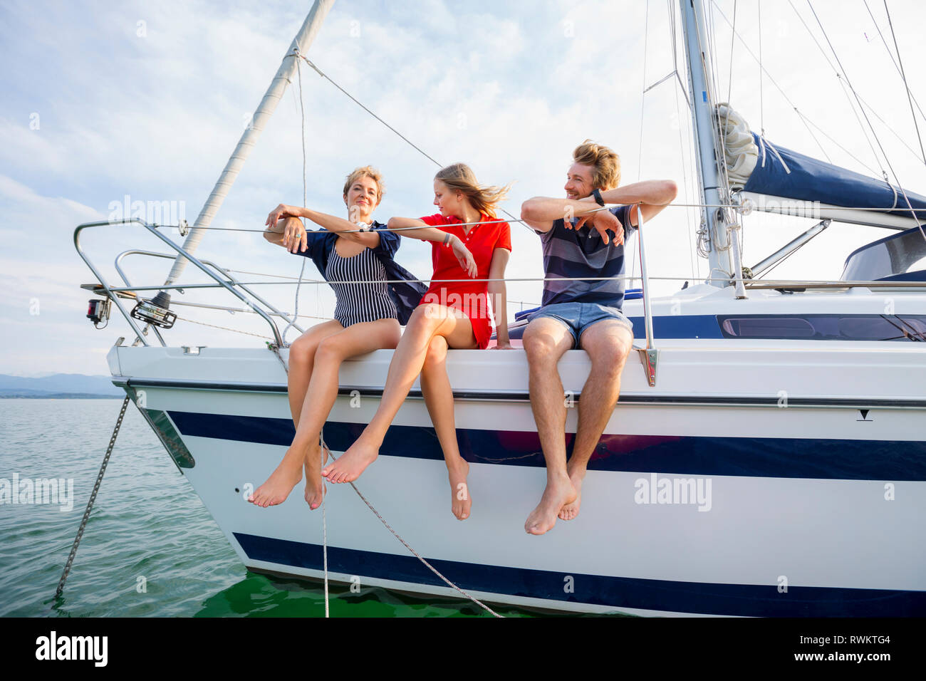 Mature woman and young adults sitting on sailboat on Chiemsee lake, Bavaria, Germany - Stock Image