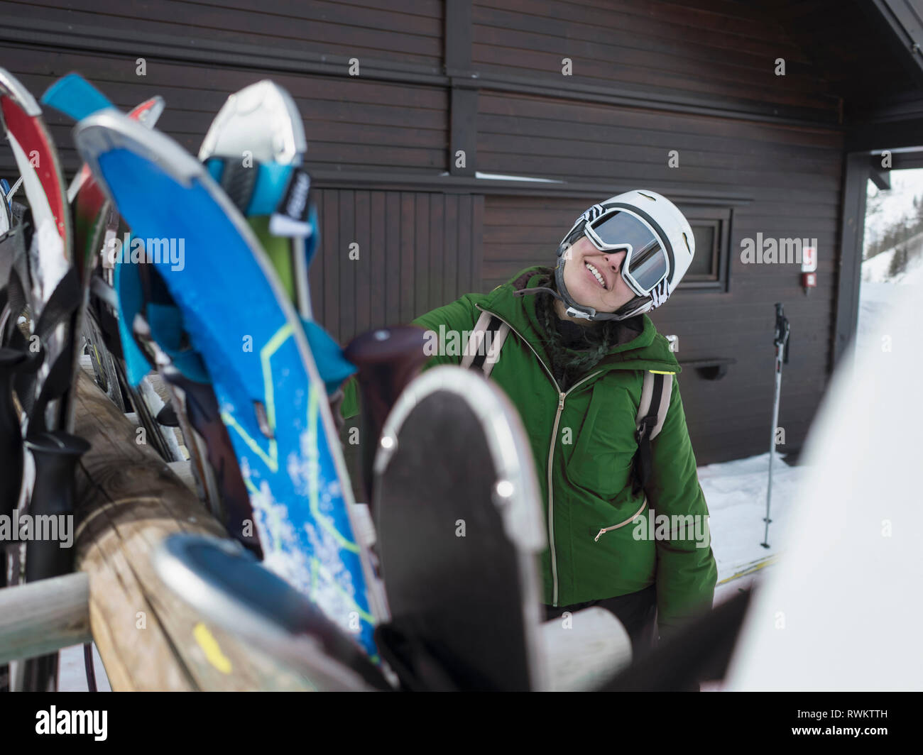 Young woman skier wearing helmet and ski goggles outside ski hut,  portrait, Alpe Ciamporino, Piemonte, Italy - Stock Image