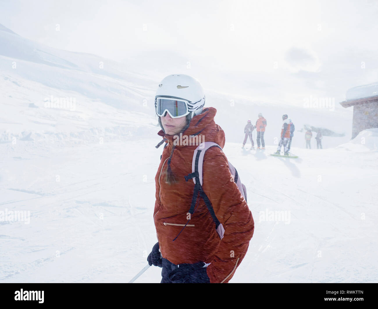 Young female skier wearing helmet and ski goggles on ski slope,  Alpe Ciamporino, Piemonte, Italy - Stock Image