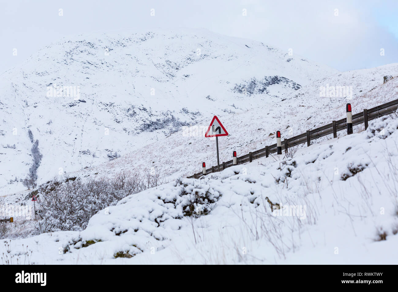 Double bend first to left road sign on A82 road on a cold winter morning with snow at Rannoch Moor, Glencoe, Argyll, Scotland - Stock Image