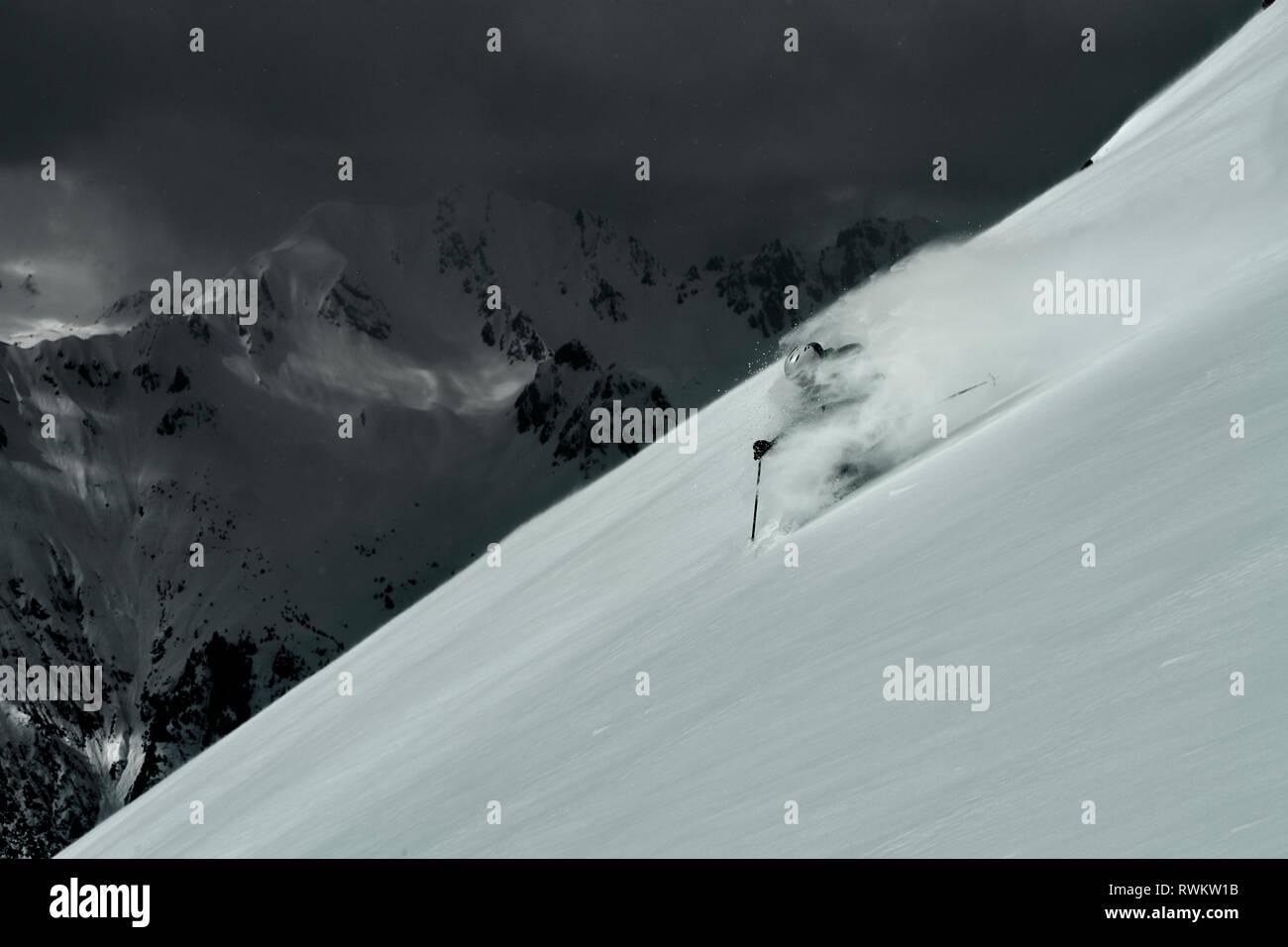 Male skier speeding down steep mountainside, Alpe-d'Huez, Rhone-Alpes, France - Stock Image