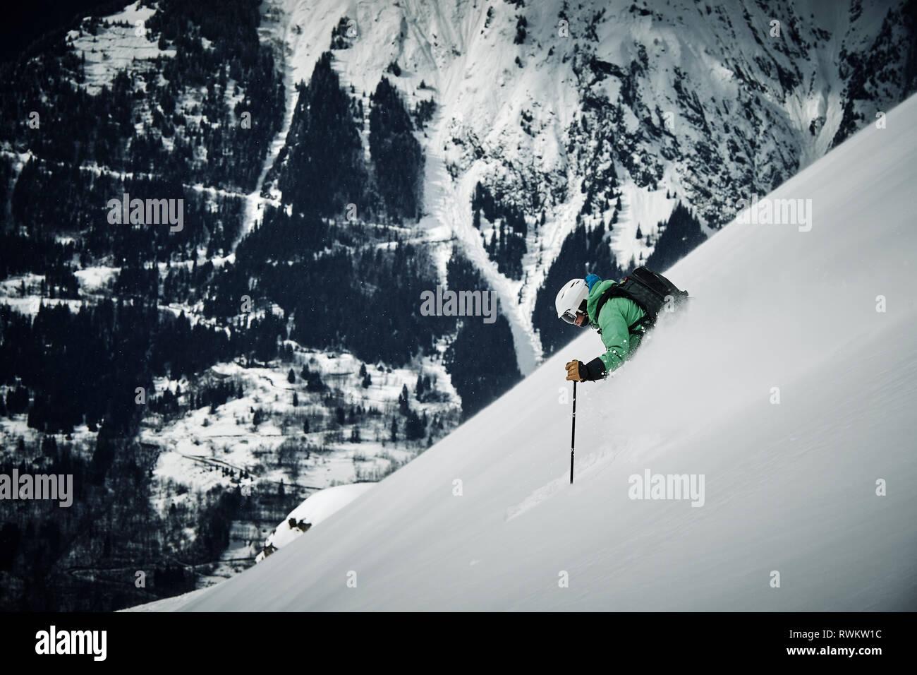 Male skier skiing down steep mountainside, Alpe-d'Huez, Rhone-Alpes, France - Stock Image