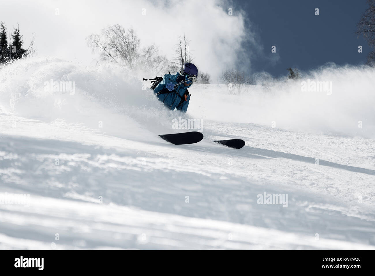 Male skier skiing down mountainside, low angle view, Alpe-d'Huez, Rhone-Alpes, France - Stock Image