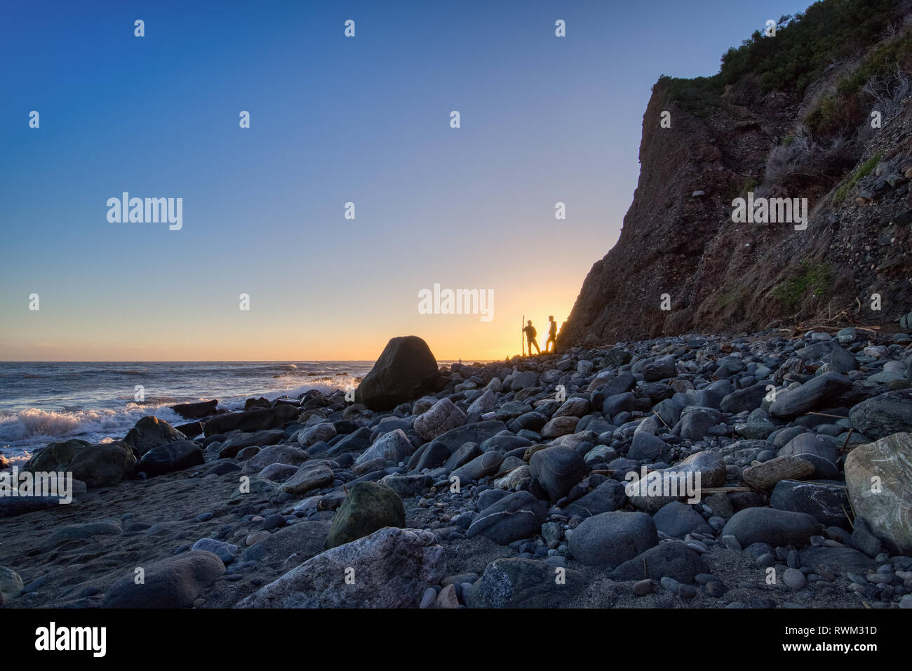Rocky shoreline view of two men standing near tall cliff at sunset with clear blue sky, Dana Point, California - Stock Image