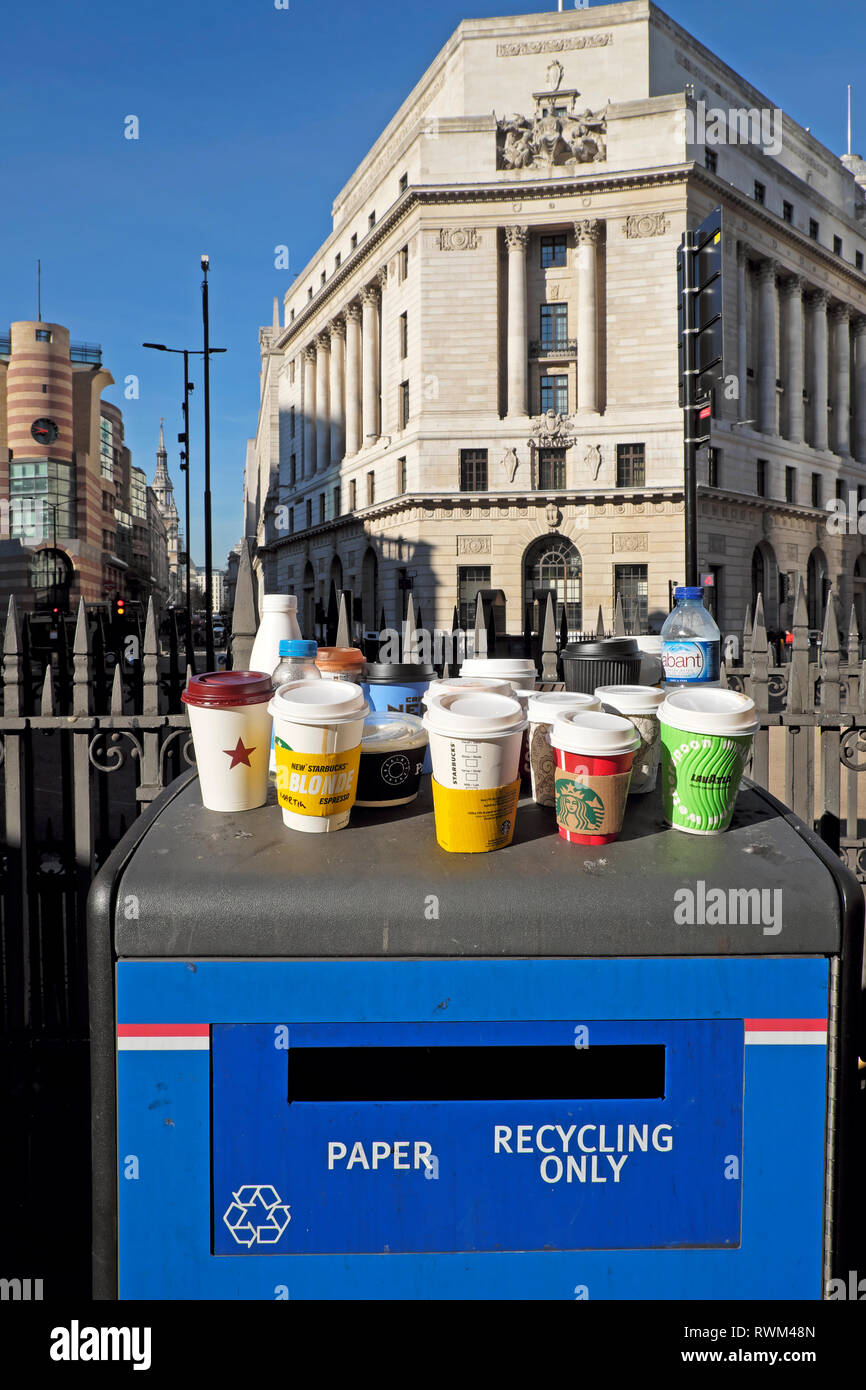 Paper and plastic empty cups and plastic bottles standing on a Paper Recycling Only waste bin Bank tube station in the City of London UK  KATHY DEWITT - Stock Image