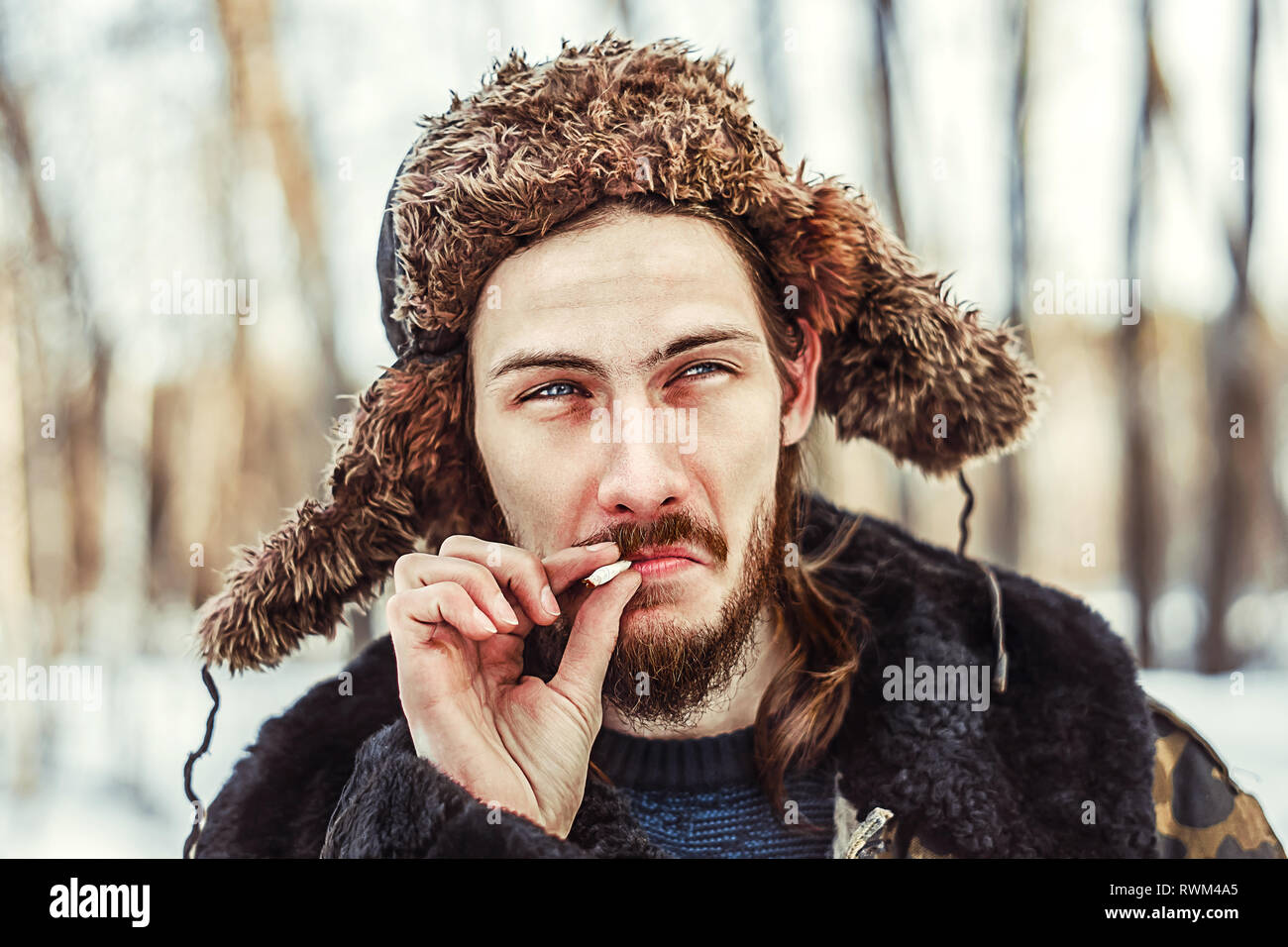 Siberian Russian man in a hat earflaps with a cigarette - Stock Image