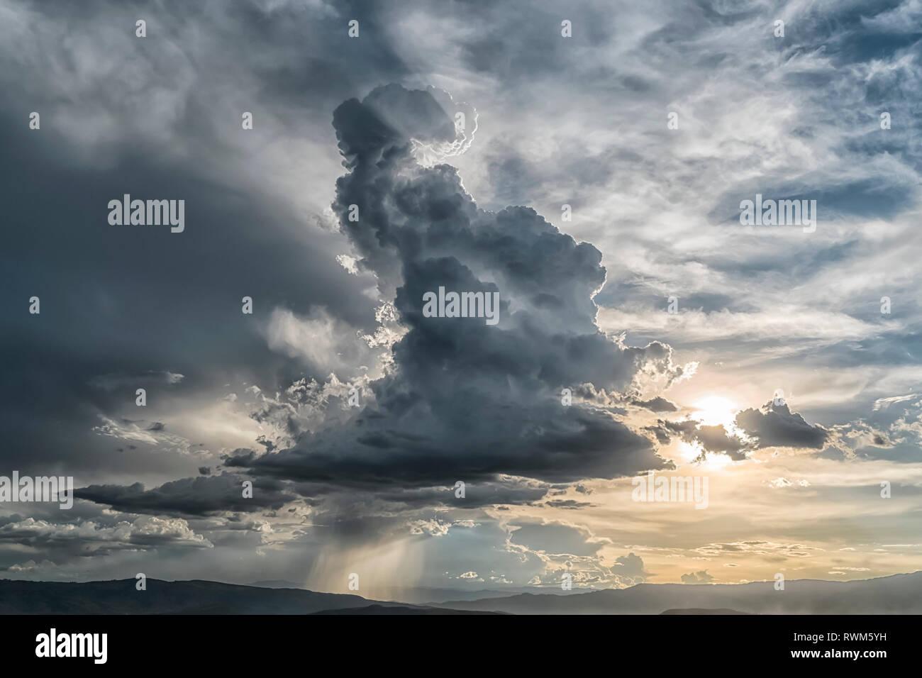 Cumulonimbus cloud building over the city of Cochabamba, Bolivia. Inspirational lighting coming from behind the cloud; Cochabamba, Bolivia - Stock Image