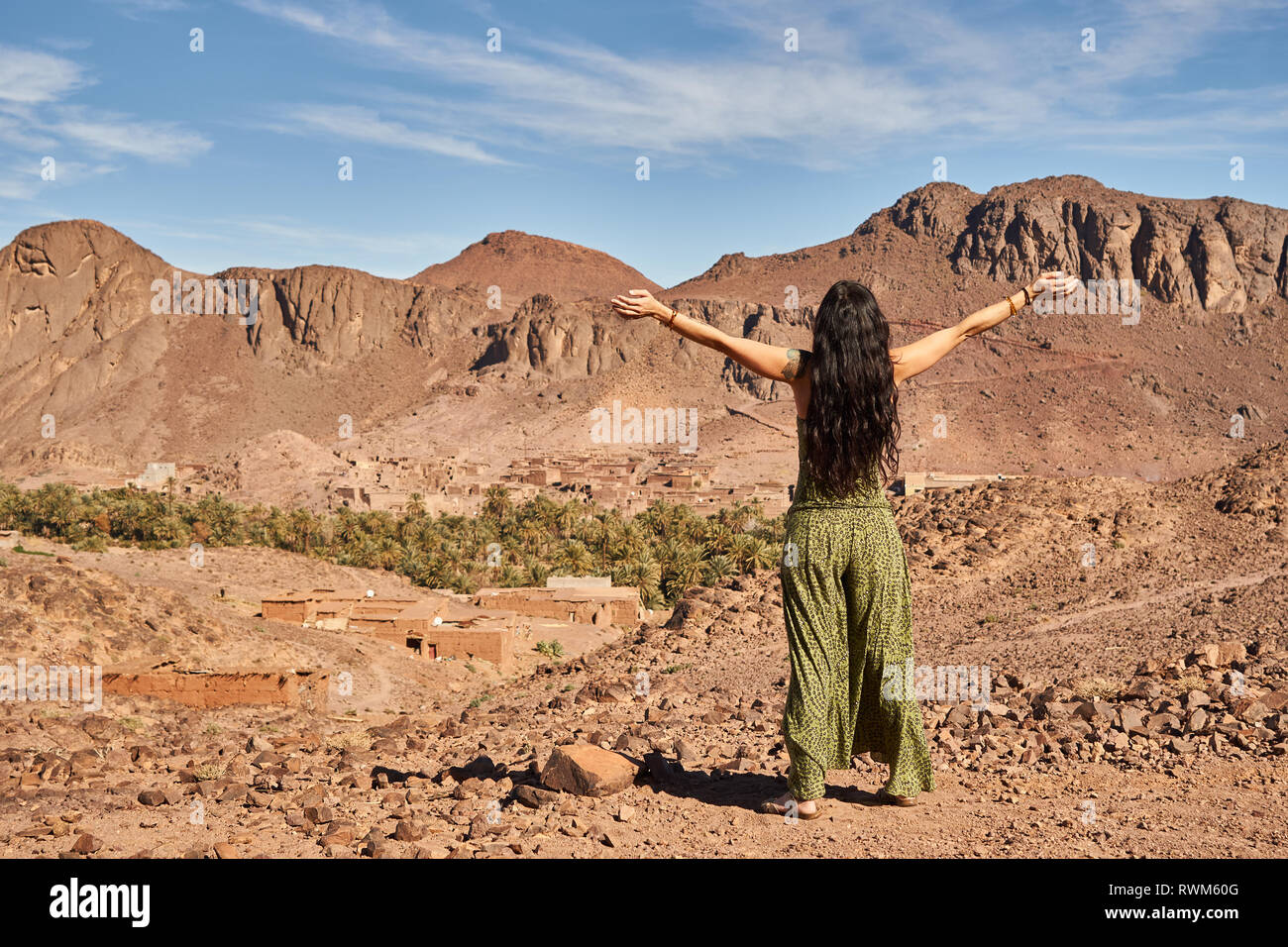 Back view of young brunette lady with hands to sides standing between desert lands near ancient constructions and hills in Marrakesh, Morocco - Stock Image