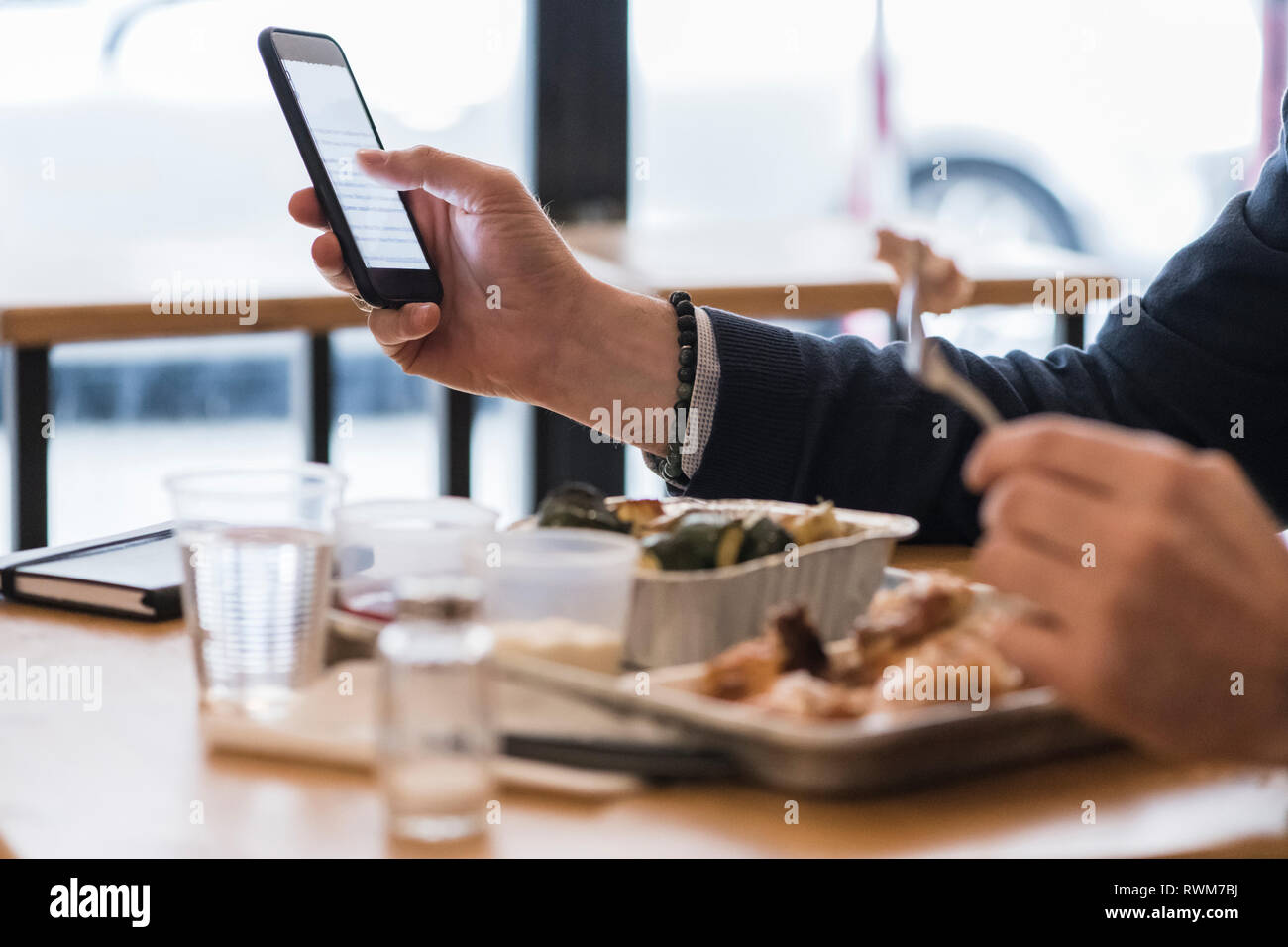 Businessman using smartphone and eating grilled chicken in