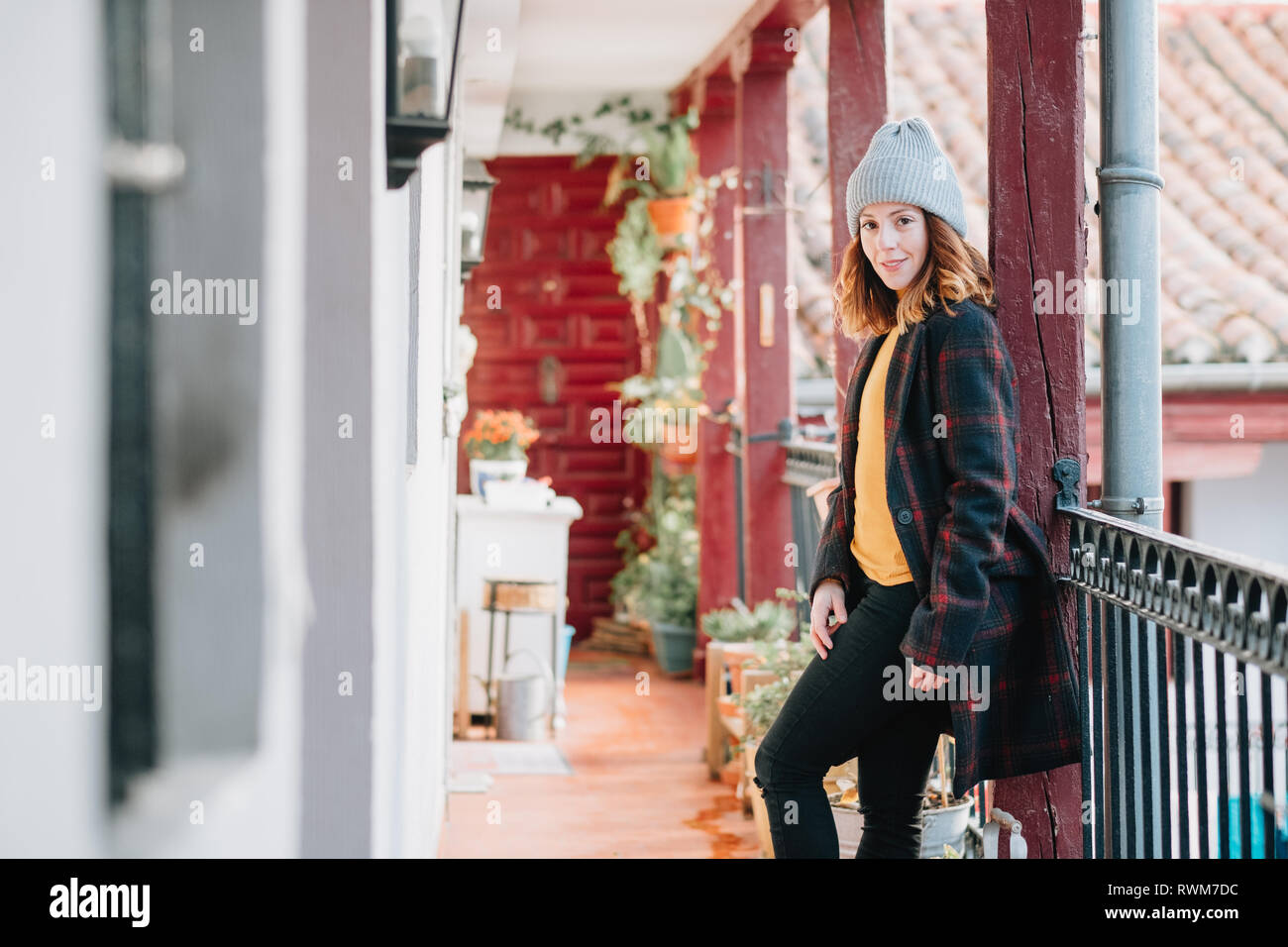 Positive attractive young lady in warm wear and hat looking away and standing near house and fence - Stock Image