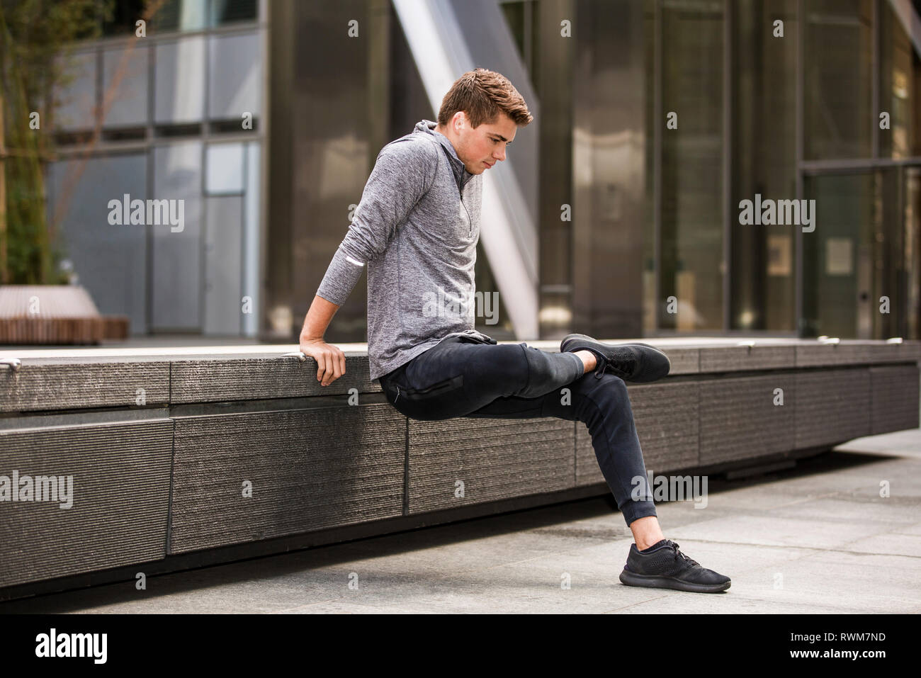 Young runner stretching on pavement, London, UK - Stock Image