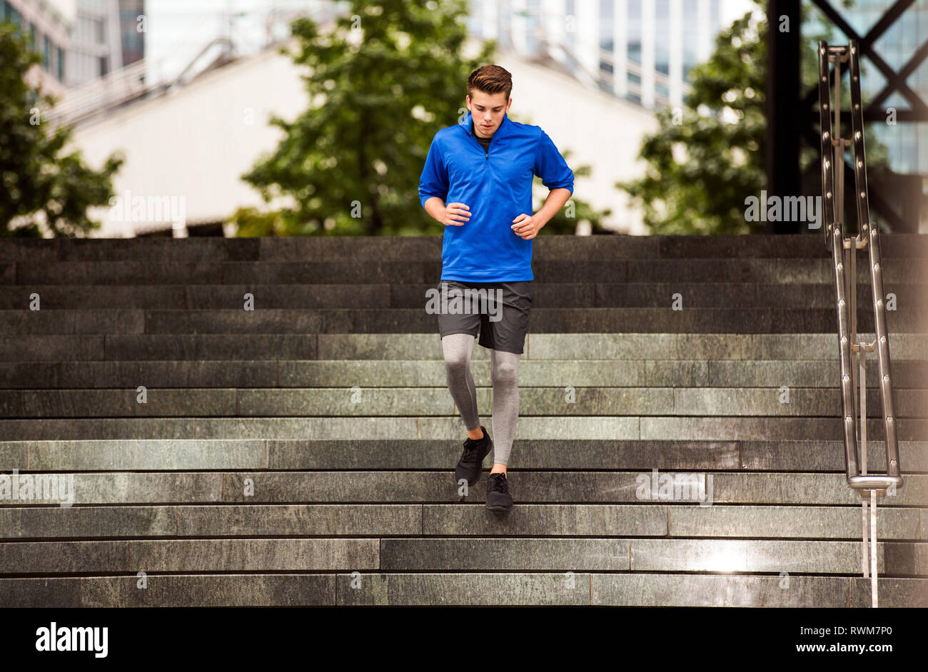 Young runner jogging down steps, London, UK - Stock Image