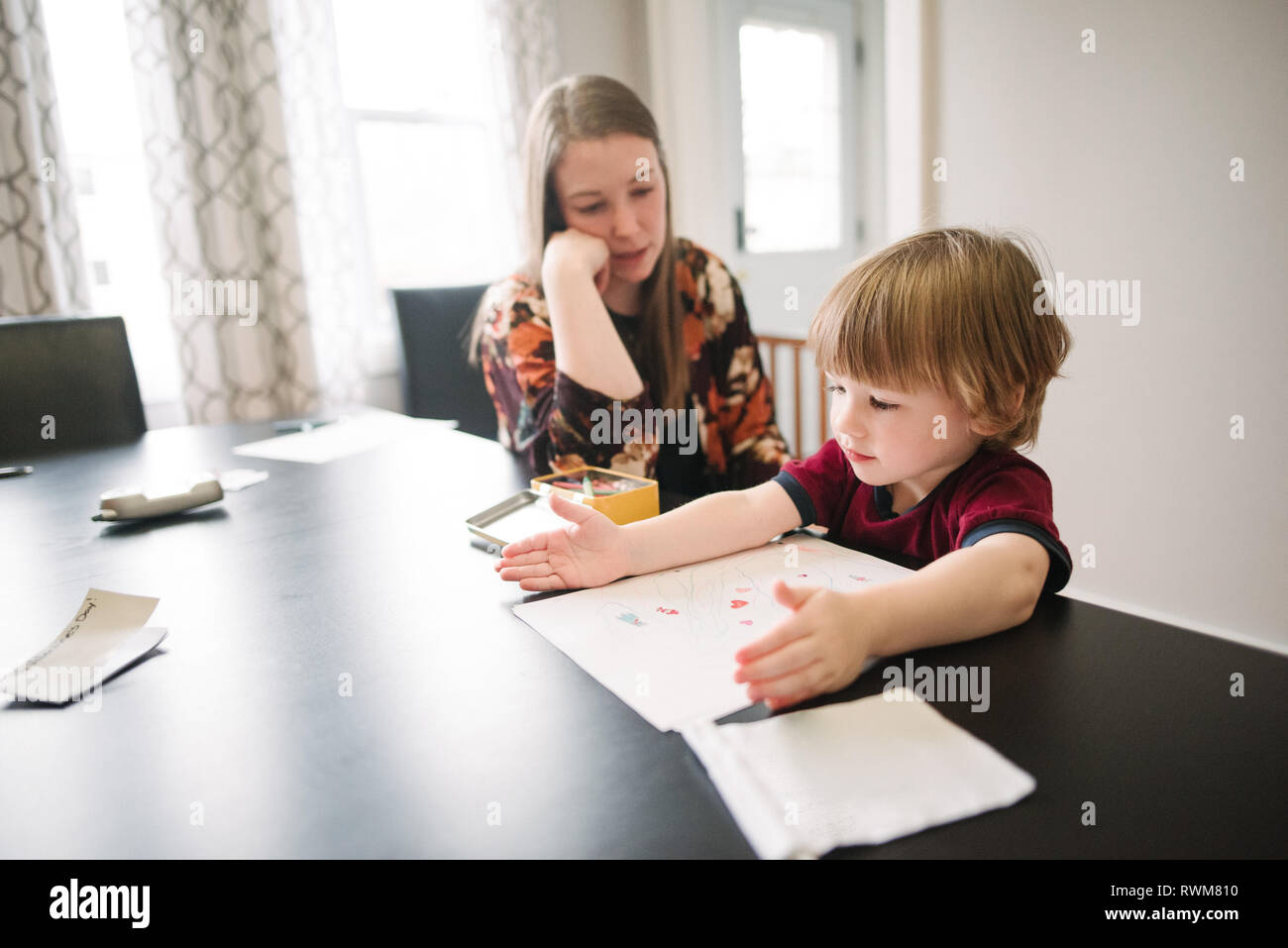 Mother watching over son learning at table Stock Photo