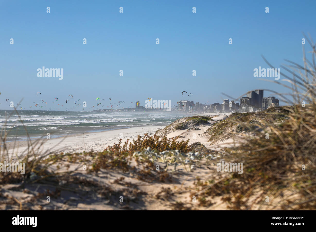 Large group of distant kite surfers mid air over sea, Cape Town, Western Cape, South Africa - Stock Image
