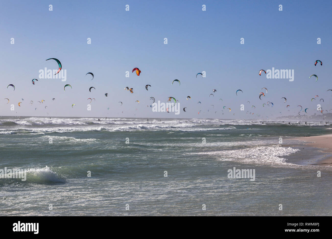 Large group of kite surfers mid air over sea, Cape Town, Western Cape, South Africa - Stock Image