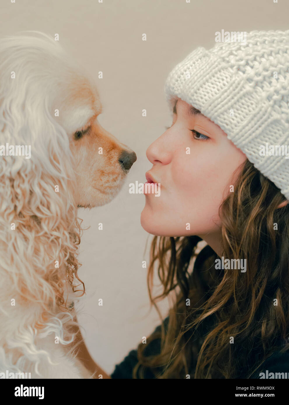 Teen in hat playing with dog - Stock Image