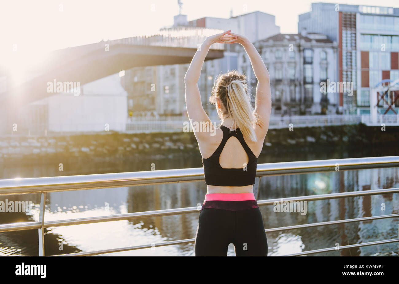 Back view of young lady in sportswear stretching hands on quay near water in city in sunny day - Stock Image