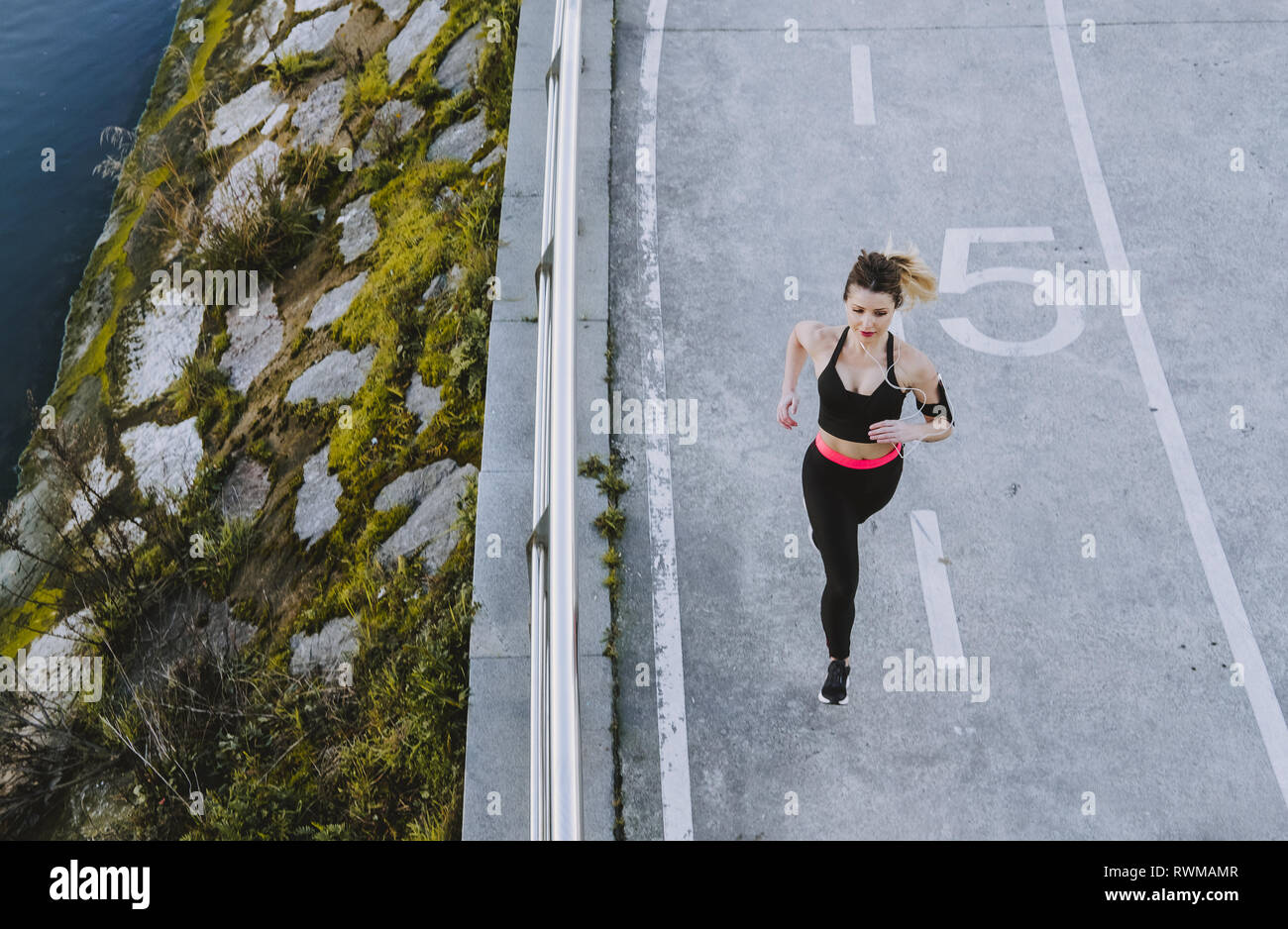 From above young lady in sportswear running on quay near water in city - Stock Image